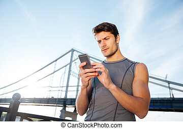 Runner using mobile smart phone and standing at the bridge -...