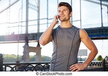 Young man in sports uniform talking on the mobile phone -...
