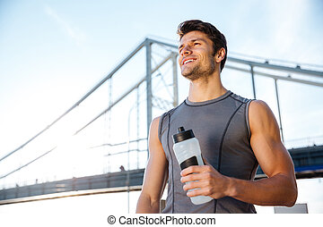 Young smiling sports man resting after running, holding water bottle