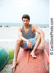 Handsome young man sitting on a fishing boat by sea -...