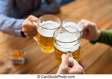 close up of hands with beer mugs at bar or pub - people,...