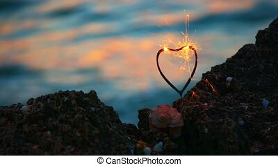 Heart shape sparkler firing in front of movins sea wavws with spot of warm sunset light, love travel concept