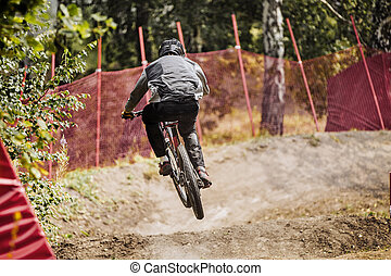 young rider athlete on bicycle jump over obstacles