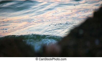 Ocean water moving swiftly with jagged rocks blurred...