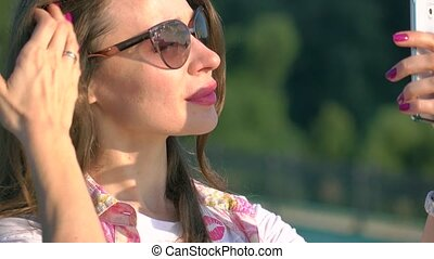 Beautiful brunette girl in sunglasses taking photo of big...