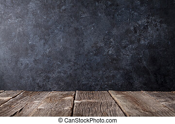 Old wooden table in front of black wall
