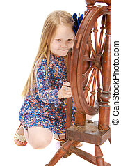 The girl looks at the spinning wheel