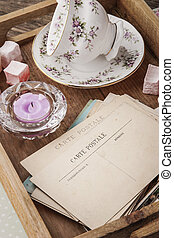 Tea things with sweets and postcards on the wooden tray...