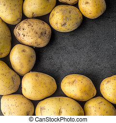 Potatoes on the dark stone table square