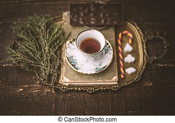 Tea set with blurred herb and chocolate on the wooden table...