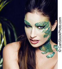 woman with creative make up like snake and rat in her hands,...