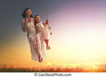 mother and daughter swinging on swings - Happy loving family...