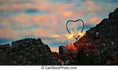 Heart shaped sparkler on the rocky coast in front of slow...