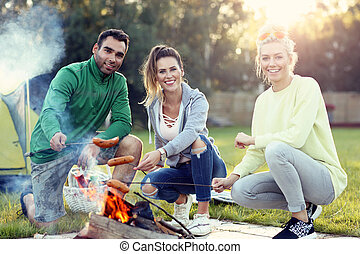 Group of friends preparing sausages on campfire
