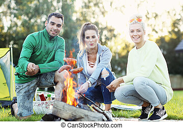Group of friends preparing marshmallow on campfire