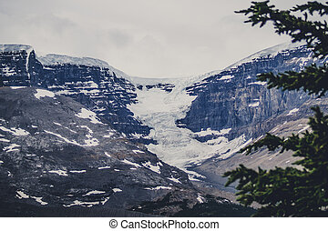 Avalanche on rough rocky mountains with snow
