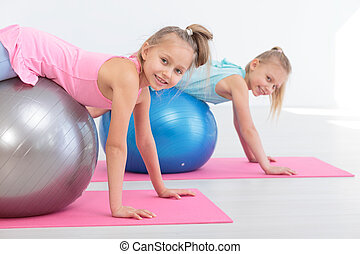 Children and exercise ball - Two girls exercising with...