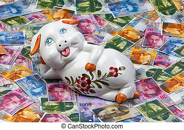 Swiss francs and piggy bank - A funny piggy bank is located...