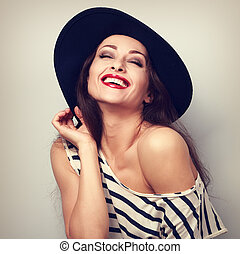 Happy toothy laughing brunette young woman in black hat with...