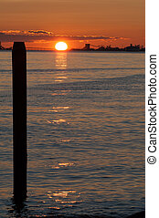 ship silhouette and post at sunset on Pacific ocean at Point...