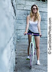 Free time for biking - Young woman summer dressed on a...