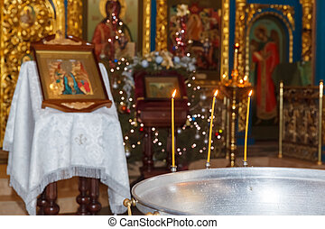 Orthodox baptism bowl of holy water and candles
