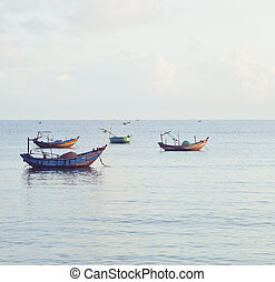 vietnameese national boats in sea at sunrise, blue clouds in...