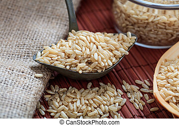 Unrefined rice and metallic old spoon - Unrefined rice in a...