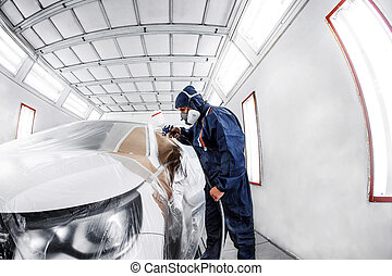 worker painting a white car in special garage, wearing...