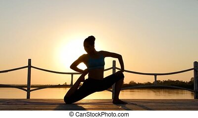 Woman practicing yoga on the beach at sunset. Healthy active...