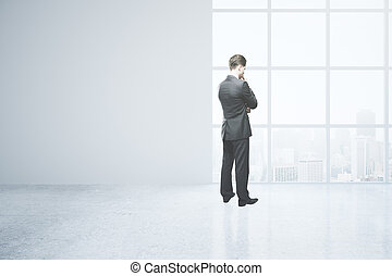 Thoughtful man in empty room - Thoughtful businessman in...