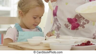 Happy little girl with empty muffin holders on table as...