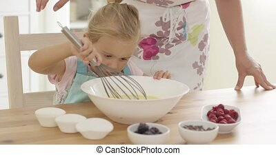 Little girl baking with her mother watching carefully as Mum...
