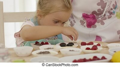Child and woman preparing muffins on table - Female child in...