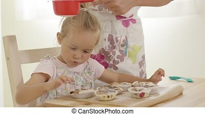 Child interested in sugar falling on baked muffins -...