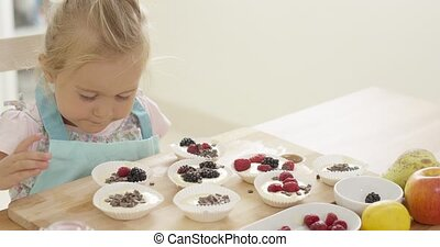 Girl putting berries on muffins on table