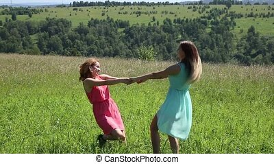 two young girlfriend circling hand in hand on the green meadow