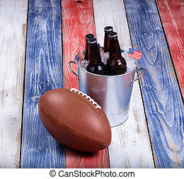 American football and ice cold beer on rustic wooden boards...