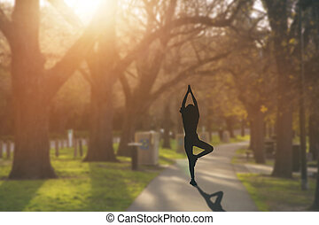 Silhouette young woman practicing yoga on public park at sunset.