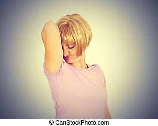 young woman, smelling, sniffing her wet armpit, something...