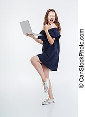 Cheerful excited young woman holding laptop and celebrating...