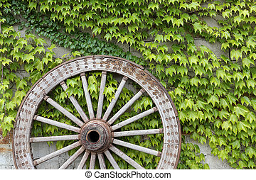 Wooden wheel on old brick wall - Antique and weathered wood...