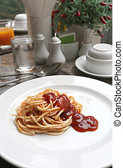 Spaghetti with tomato sauce on white dish.
