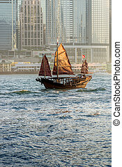 Old Junk on Hong Kong harbour with the sunlight hitting the...