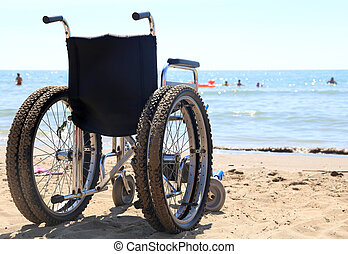 wheelchair aluminum on the sand of the beach to the sea