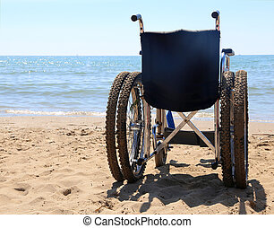 wheelchair on the sand of the beach - big wheelchair on the...