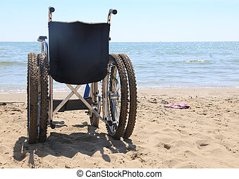wheelchair on the beach by the sea in summer