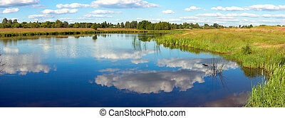 Summer rushy lake panorama view with clouds reflections. Six...