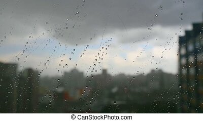 Urban view of rain drops falls on a window during a stormy day overlooking city skyline in the background