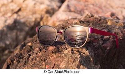 sunglasses which reflect - sunglasses lying on a rock and...